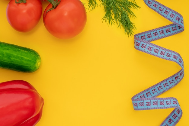 Pomodoro, cetriolo, pepe, aneto, metro a nastro su uno sfondo giallo brillante, vista dall'alto, piatto, copia spazio. concetto di alimentazione sana, slim