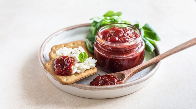 Confettura di confettura di pomodoro o salsa con cracker e insalata insolita marmellata salata cucina mediterranea