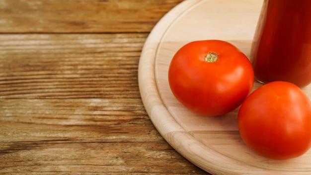 Succo di pomodoro, pomodori freschi su fondo di legno - foto orizzontale