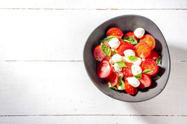 Insalata caprese di mozzarella di pomodoro con basilico e olio d'oliva su fondo di legno bianco