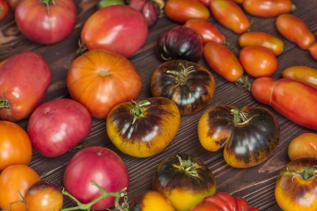 Pomodoro sul vecchio legno. pomodori freschi grandi e piccoli su fondo di legno scuro.