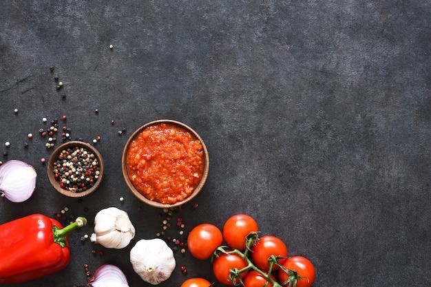 Salsa di pomodoro con pepe e aglio su uno sfondo scuro di cemento.