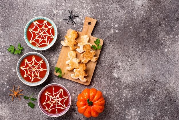 Zuppa di pomodoro e pane a forma di uomo. dolcetti di halloween per la festa.