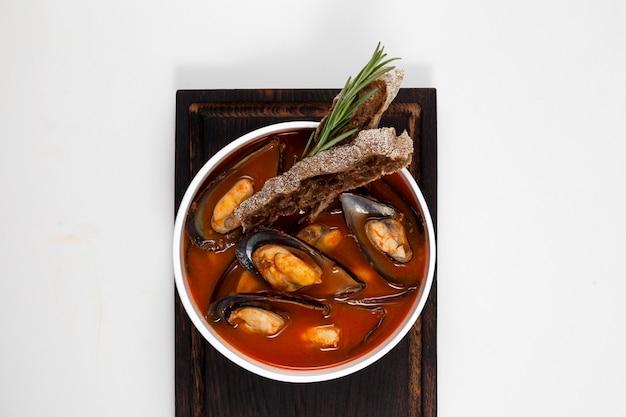 Zuppa di pomodoro con cozze. servito con crostini di segale, guarnito con un rametto di rosmarino.