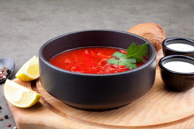 Zuppa di pomodoro con verdure, decorato con prezzemolo, in un piatto nero, su una tavola di legno. minestre di concetto o cibo sano.
