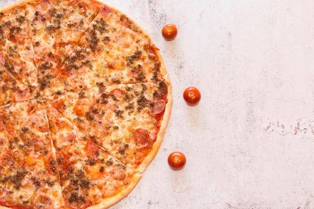Pomodori intorno a una pizza. pizza su struttura rustica e bianca. ingredienti naturali e freschi. cibo veloce fatto in casa.