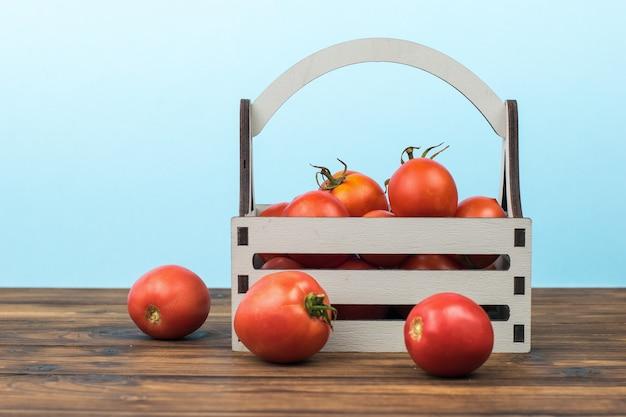 Pomodori in una scatola sul tavolo su sfondo blu.