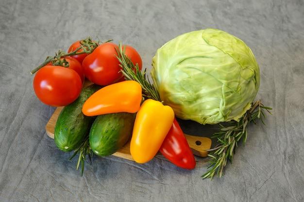 Pomodori, cavoli, peperoni dolci e cetrioli su sfondo grigio