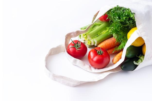 Pomodori, cetrioli, carote, lattuga verde sedano e limone in sacchetto di lino riutilizzabile eco naturale in tessuto isolato su una superficie bianca