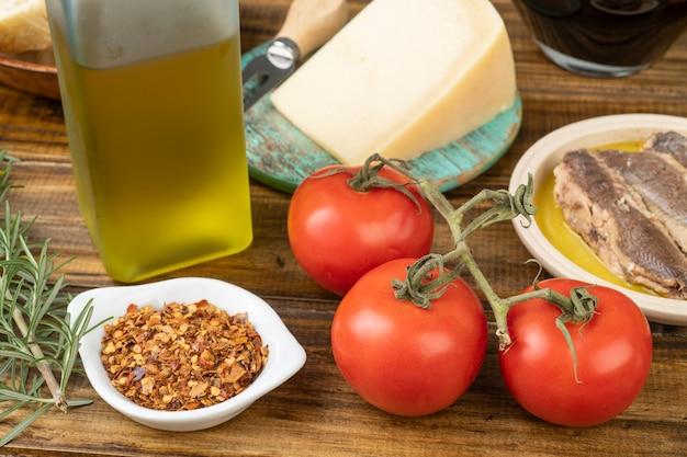 Pomodori, pesce, olio d'oliva, vino, parmigiano ed erbe aromatiche su un tavolo di legno. cibo mediterraneo.