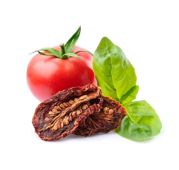 Verdure di pomodori con pomodoro secco con foglie di basilico in primo piano.
