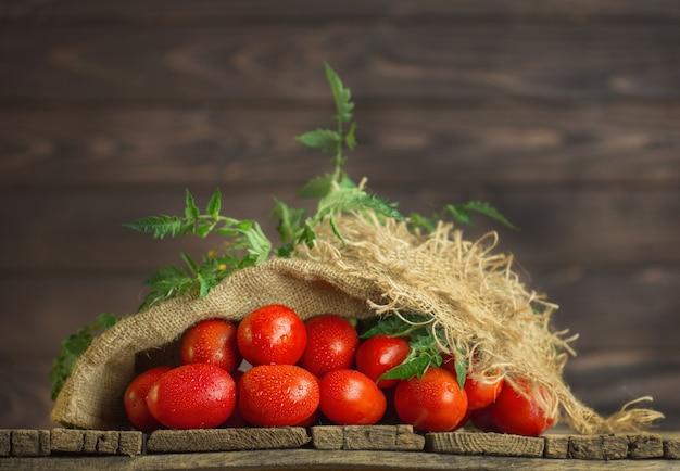 Pomodori sulla tavola di legno. cumulo di pomodori freschi nel sacchetto di tela ruvida sul tavolo di legno. concetto di prodotto naturale.