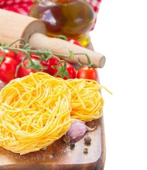 Tonarelli pasta cruda con pomodoro e olio d'oliva isolato su bianco