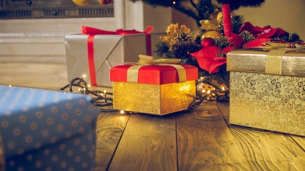 Sfondo di natale tonico. confezione regalo dorata, ghirlanda e luci incandescenti sul pavimento in legno del soggiorno