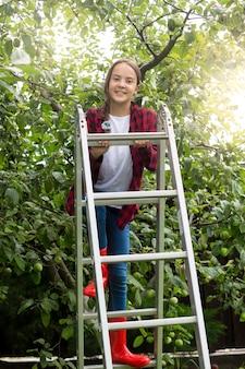 Immagine tonica dell'adolescente felice che posa sulla scala a pioli al giardino delle mele