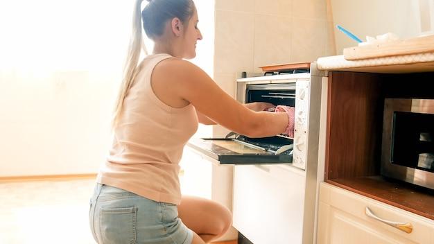 Foto tonica di una bella casalinga sorridente che mette una teglia con biscotti crudi nel forno caldo in cucina