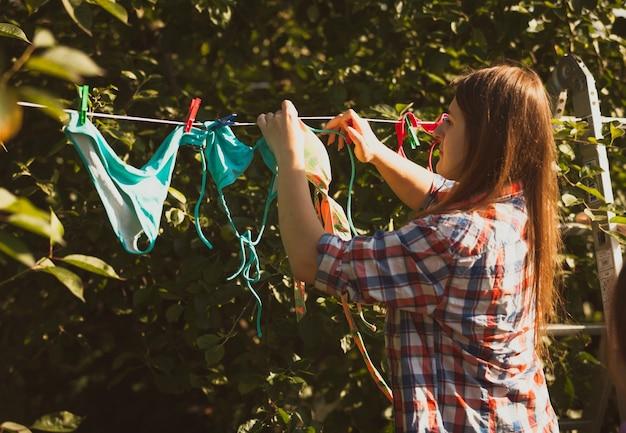 Foto tonica di bella donna che asciuga i costumi da bagno sulla corda da bucato