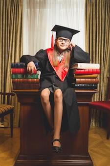 Foto tonica della bambina con il berretto da laurea in posa sul tavolo in biblioteca