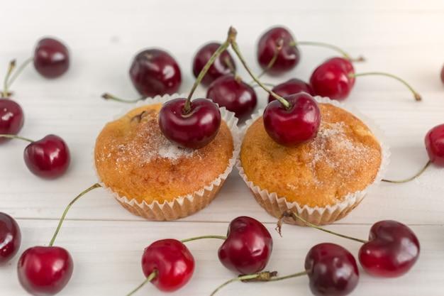 Foto tonica di due muffin decorati con ciliegie fresche