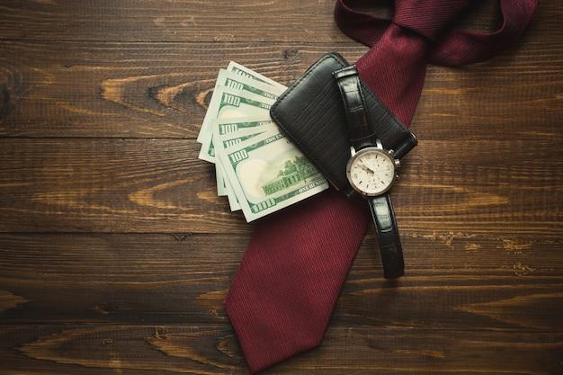 Foto tonica di orologi da polso, soldi in borsa e cravatta rossa su sfondo di legno scuro
