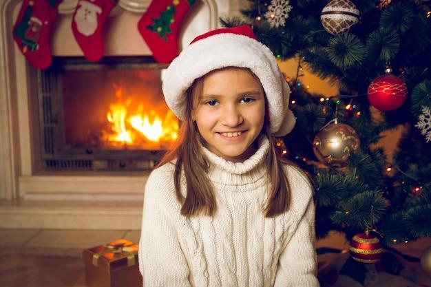 Ritratto tonico di una ragazza allegra con un cappello da babbo natale seduto accanto al caminetto acceso a casa