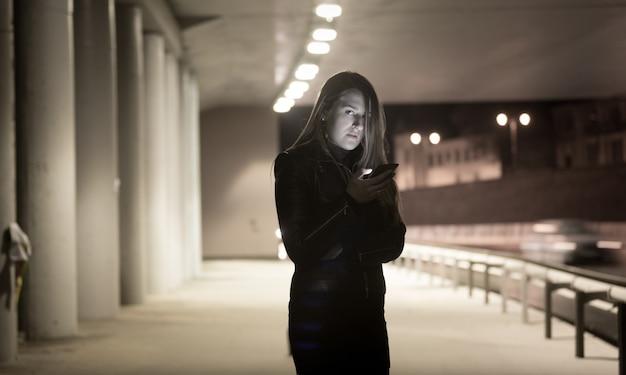 Ritratto tonico di donna sola che usa il cellulare di notte per strada