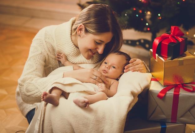 Ritratto tonico di giovane madre che bacia bambino sdraiato nel soggiorno decorato per natale