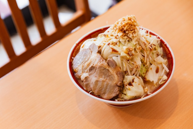 Tonkotsu chashu ramen condito con cavolo, beansprout e aglio servito in porzione di grandi dimensioni.