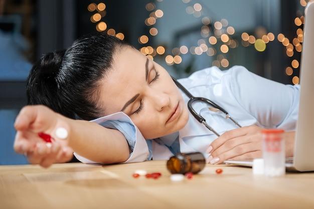Troppo esausto. scienziato femminile che lavora sodo stanco che tiene le pillole in mano e dorme mentre è troppo esausto