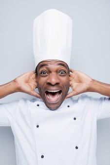 Troppo sale! eccitato giovane chef africano in uniforme bianca che tocca la testa con le mani