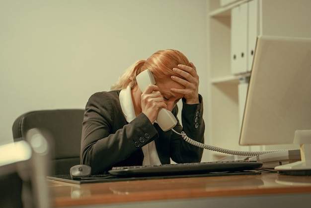 Troppo lavoro assonnato ha sottolineato la giovane donna seduta alla sua scrivania davanti al computer. programma occupato al college, sul posto di lavoro, concetto di privazione del sonno