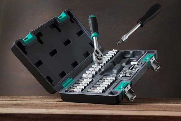 Cassetta degli attrezzi. scatola con strumenti su un tavolo di legno, cacciavite, chiave inglese con ugelli. set di attrezzi per auto.