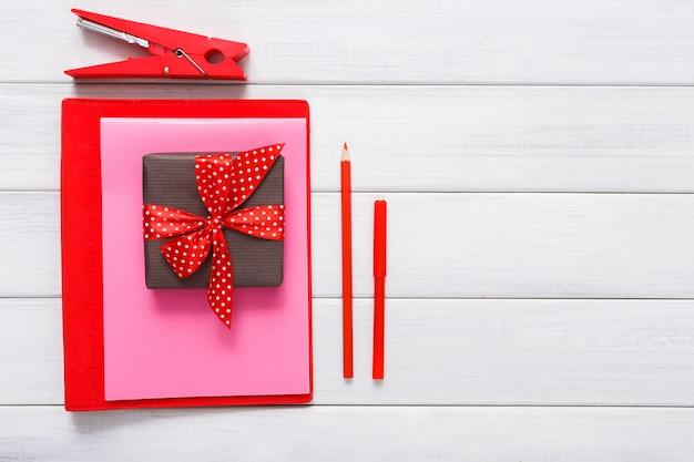 Strumenti per creare biglietti, matite per tagliare e incollare, carta colorata e scatola regalo su legno bianco