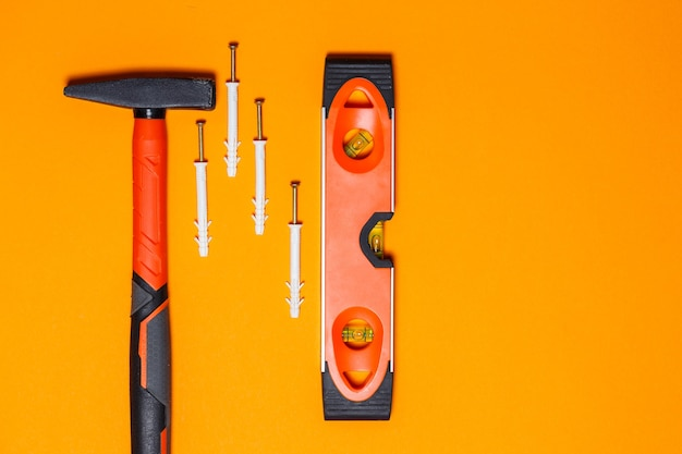 Strumenti per la riparazione. martello per chiodi, livella, tassello nel muro su sfondo arancione. toolkit per il mago