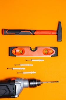 Strumenti per la riparazione di uso domestico. martello per chiodi, livella e trapano, tassello nel muro su sfondo arancione. toolkit per il mago