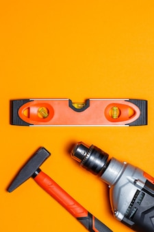 Strumenti per la riparazione di uso domestico. martello per chiodi, livella e trapano su uno sfondo arancione. toolkit per il mago