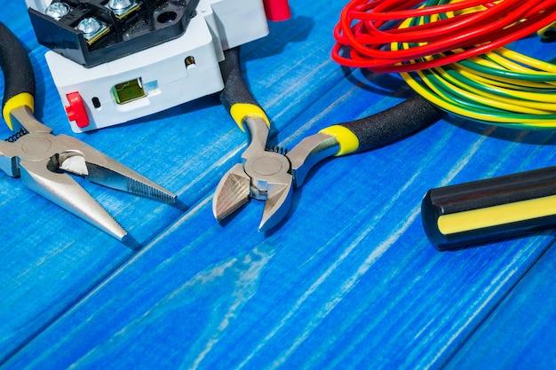 Strumenti e pezzi di ricambio per il maestro elettricista su tavole di legno blu