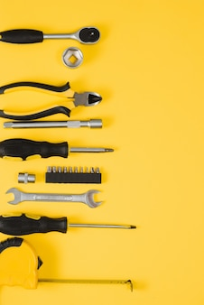 Strumenti vista dall'alto su sfondo giallo. pinza, chiavi aperte, cacciaviti e pinzatrice piatta laici con spazio di copia.