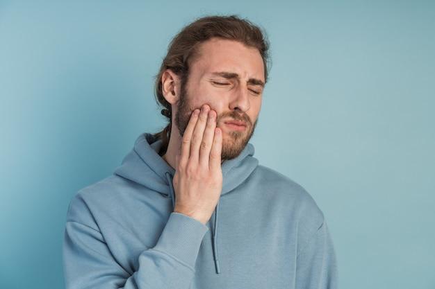 Mal di denti giovane che sente dolore, tenendosi la guancia con la mano