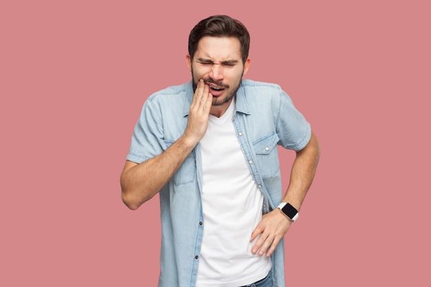 Mal di denti o dolore. ritratto di triste giovane barbuto malato in camicia blu stile casual in piedi e toccando il suo chik perché sente dolore sul dente. girato in studio al coperto, isolato su sfondo rosa.