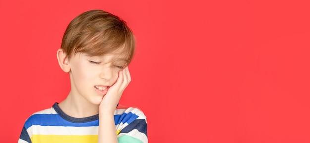 Antidolorifico per il mal di denti. malattia dentale. mal di denti come dolore dentale. concetto di dentista. il ragazzo del ritratto ha mal di denti. concetti di igiene orale