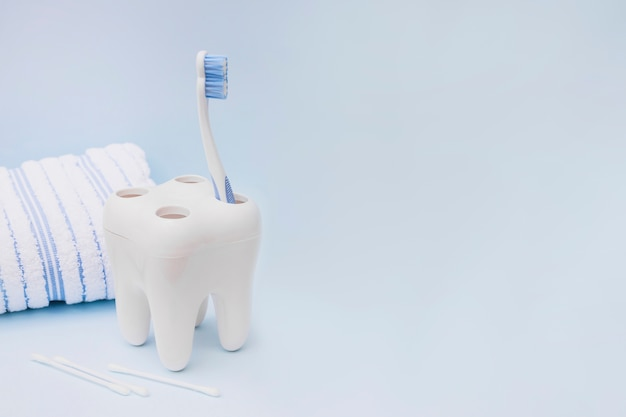 Spazzolino da denti; tampone di cotone e asciugamano su sfondo blu