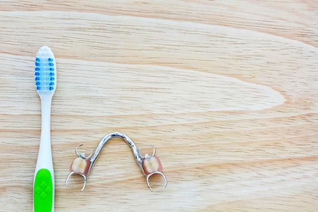 Spazzolino da denti e dentiera su fondo di legno