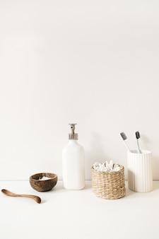 Spazzolini da denti, bastoncini per le orecchie, crema di sapone liquido sul tavolo bianco