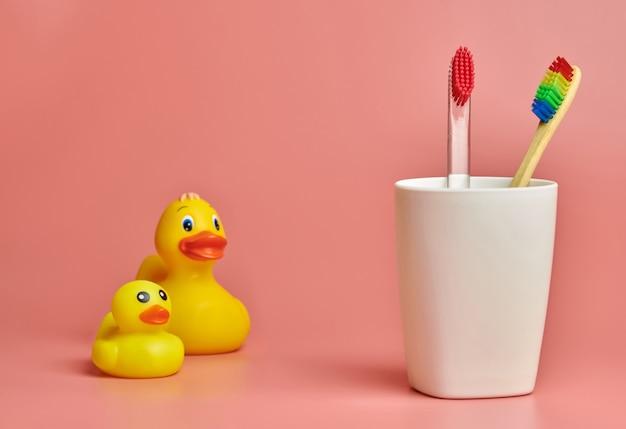 Spazzolini da denti in bicchiere di plastica e anatra giocattolo