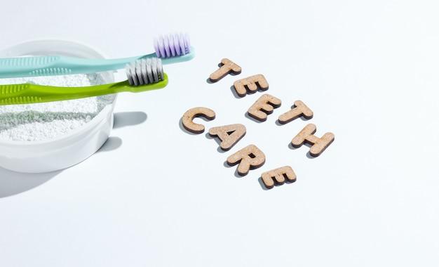 Spazzolini da denti e denti in polvere isolati su bianco