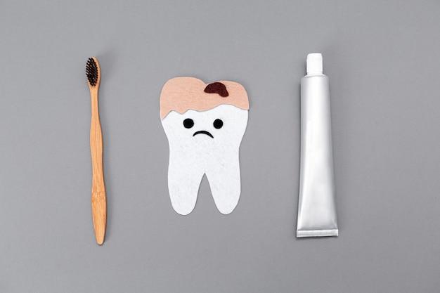 Dentifricio, uno spazzolino da denti di bambù e un dente pieno di carie scolpito nel feltro con una faccia da cartone animato. lay piatto il concetto di prodotti per la cura personale ecologici.