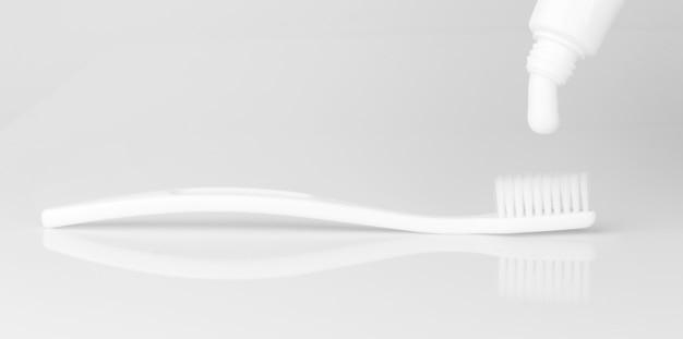 Dentifricio e spazzolino da denti isolati su sfondo bianco