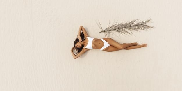 Vista aerea superiore del fuco della donna in bikini del costume da bagno che si rilassa e che prende il sole sulla spiaggia