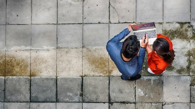 Vista aerea superiore dell'uomo d'affari e della donna che si incontrano e utilizzano il computer.